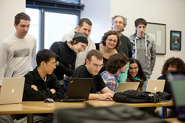 David Fan and Bob Adolf (left and center, seated at laptops) were second-place finishers in the IACS Computational Challenge.  For the final challenge, students were tasked with designing a program to play foosball.