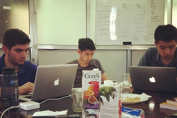 Three members of the Tech in the World team work at their computers at the APHFTA offices in Dar es Salaam on Christmas Day. From left are Harvard undergraduates Salvatore Rinchiera, Joshua Lee, and Brandon Liu.
