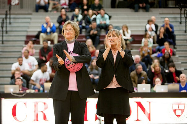 President Drew Faust (left) was presented with a pink basketball by fellow cancer survivor and women's basketball coach Kathy Delaney-Smith in honor of the Pink Zone, a special event that supports the fight against breast cancer.