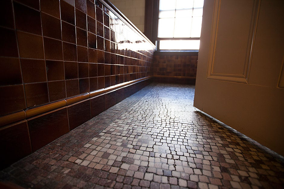 Worn and random brown tesserae are patterned on the floor of the 1891 bathroom.