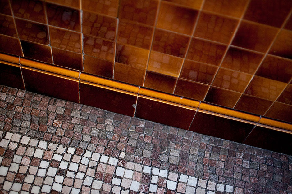 The floor's mosaic is reflected in the tub's shiny tile base.