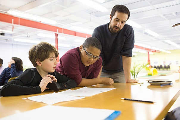 Luke Black (left) and Michael Emery work on their play at the Harvard Allston Education Portal with Brendan Shea, an A.R.T. education and community programs associate.