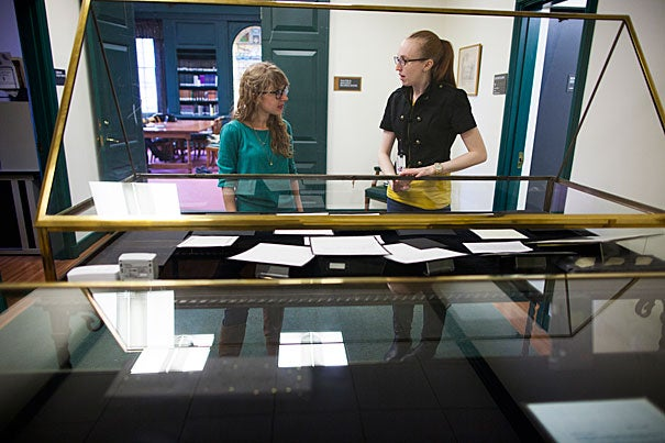 Graduate student Caitlin Schmid (left) and Carly Weggeland of the Weissman Preservation Center work on the five-case exhibit featuring  Paul Fromm's work.