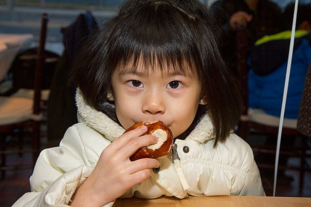 Violet Huang, 5, of Allston, samples a pretzel ball at the opening of new Barry's Corner bakery, Swissbäkers.