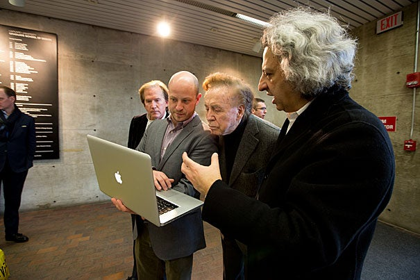 Ben Prosky (second from left), GSD's assistant dean for internal and external communications, shows John Portman Jr. and GSD Dean Mohsen Mostafavi pictures of an exhibit that is being installed in the lobby of Gund Hall. The GSD has established the John Portman Visiting Chair in Architecture in honor of Portman.