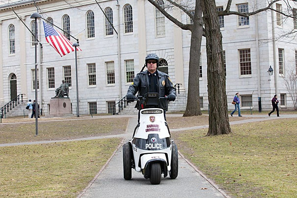 Harvard University Police Department Sgt. Bill Chipman rides a new, greener police vehicle in the Yard. Officers will now use these fully electric, three-wheeled vehicles to maintain public safety during regular patrols and special events.