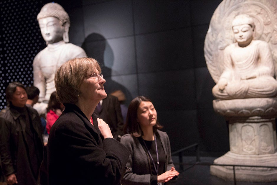 Harvard President Drew Faust explores the National Museum of Korea in Seoul with Jae Uk Chong (far left), an alumnus of the Harvard Graduate School of Design and a professor at Dankook University's College of Architecture. Eun Ji Kim (right), a museum tour guide, offers historical information about the Buddha statues.