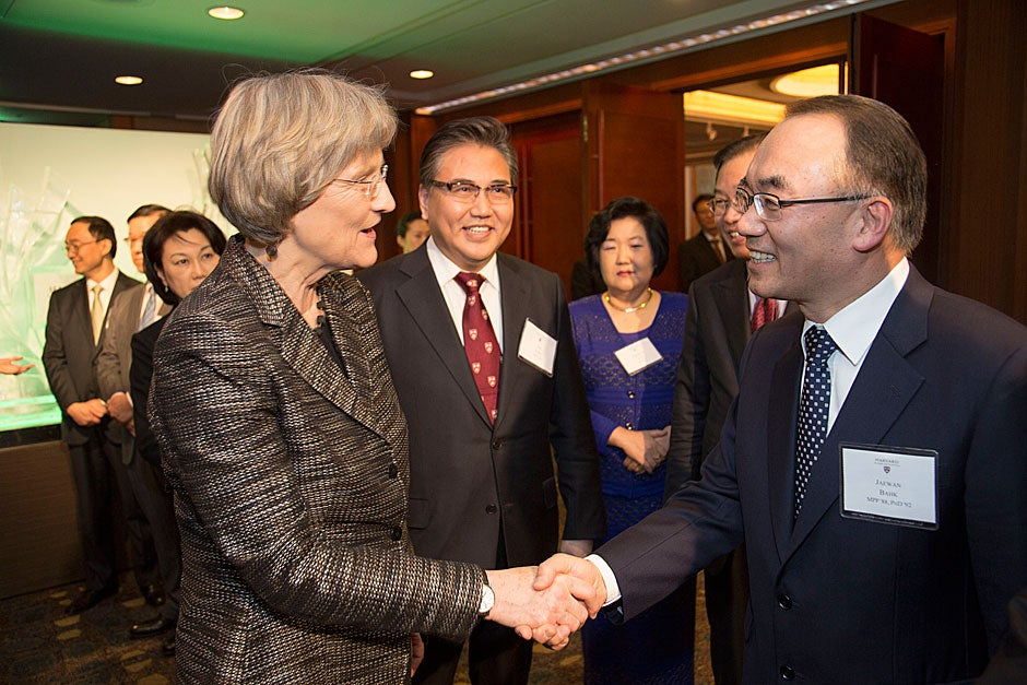 Harvard President Drew Faust shakes hands with Jaewan Bahk, M.P.P. '88, Ph.D. '92, as Jin Park, M.P.A. '85 (next to Faust), looks on during the HAA dinner in Seoul.