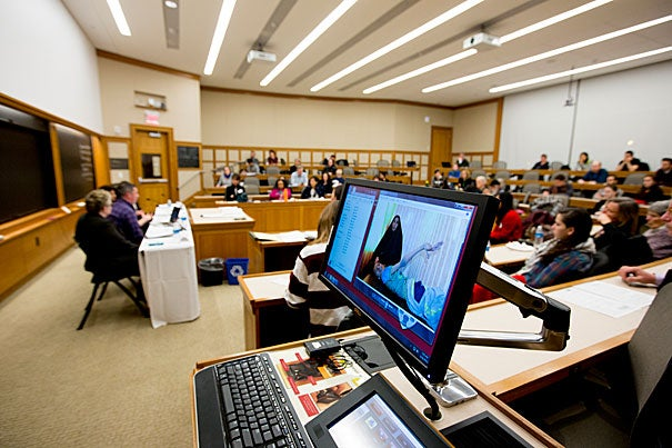 A picture of an Iraqi child suffering from a congenital disorder and his mother is displayed on a computer screen during a discussion about the war in Iraq. (Critics of the war argue that high rates of birth defects and children born with other ailments in certain areas of Iraq are an under-reported legacy of the war.) Panelists Yanar Mohammed, Matt Howard, and Pamela Spees — all representing human rights organizations — gathered at Harvard Law School to reflect on the lasting impact of the Iraq and Afghanistan wars.