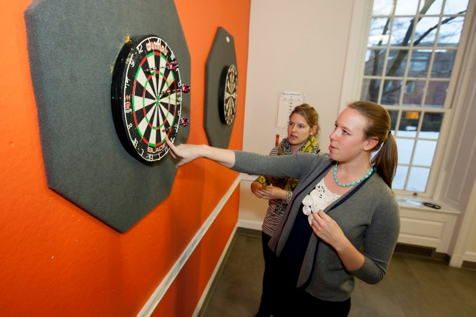 Seniors Audrey Anderson (left) and Sophie Bearman try to make sense of the scoring system while playing darts.