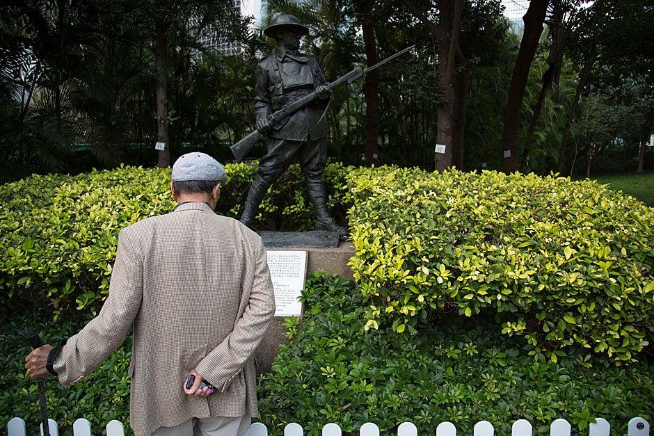 A man views a military statue in the Hong Kong Park.