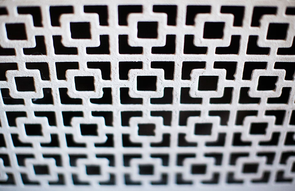 In stark black and white, a lattice of decorative squares adorns a vent inside a Harvard Hall lecture room.