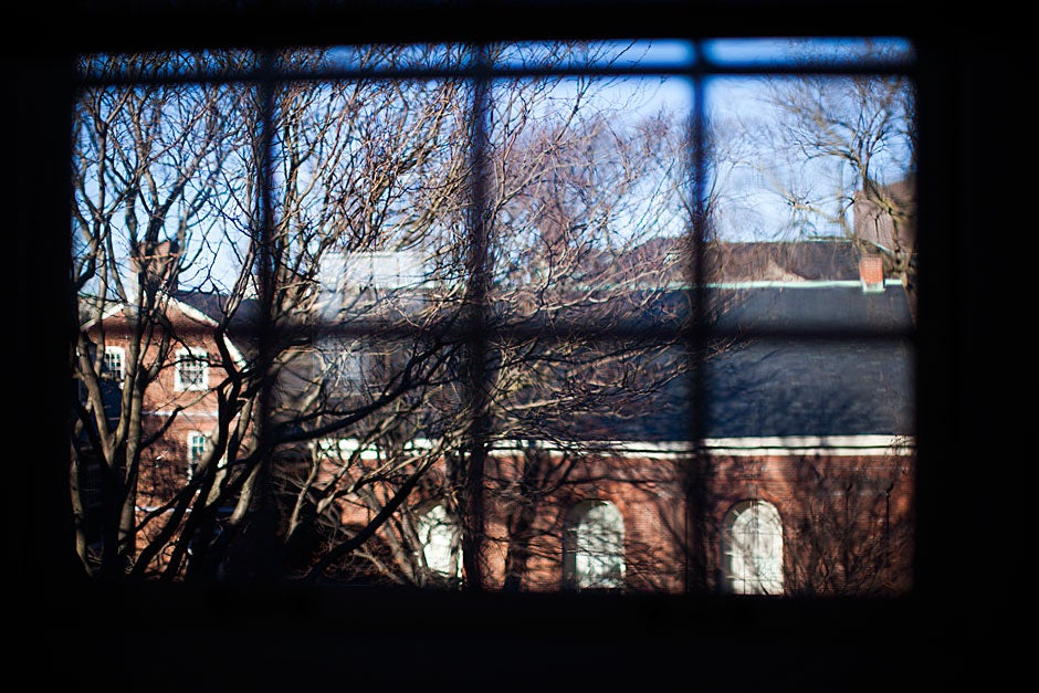 Holden Chapel, built in 1744 and among the oldest buildings in Harvard Yard, is framed in the windowpanes of Harvard Hall.