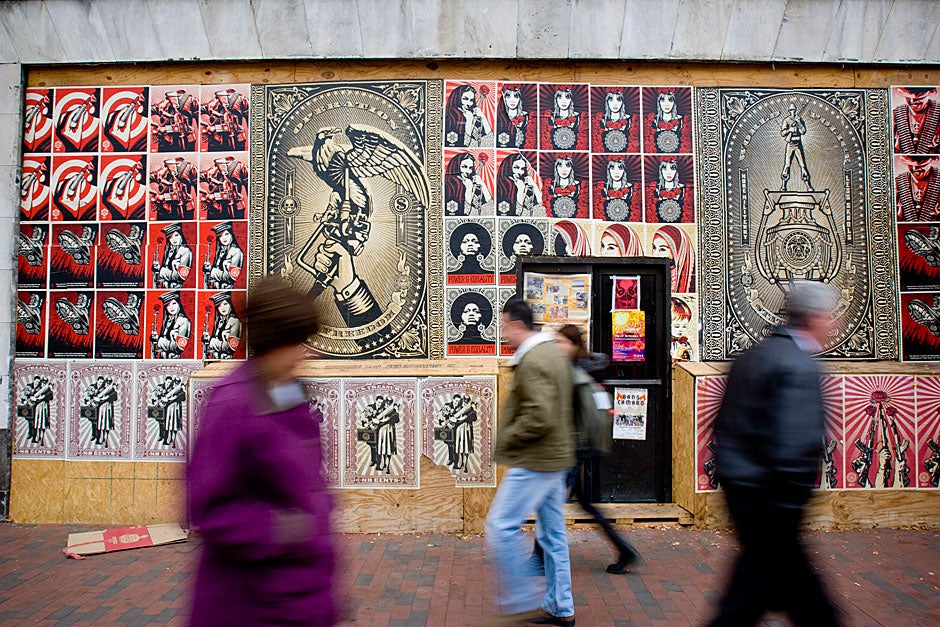 Shepard Fairey posters decorate a storefront construction site on Brattle Street.