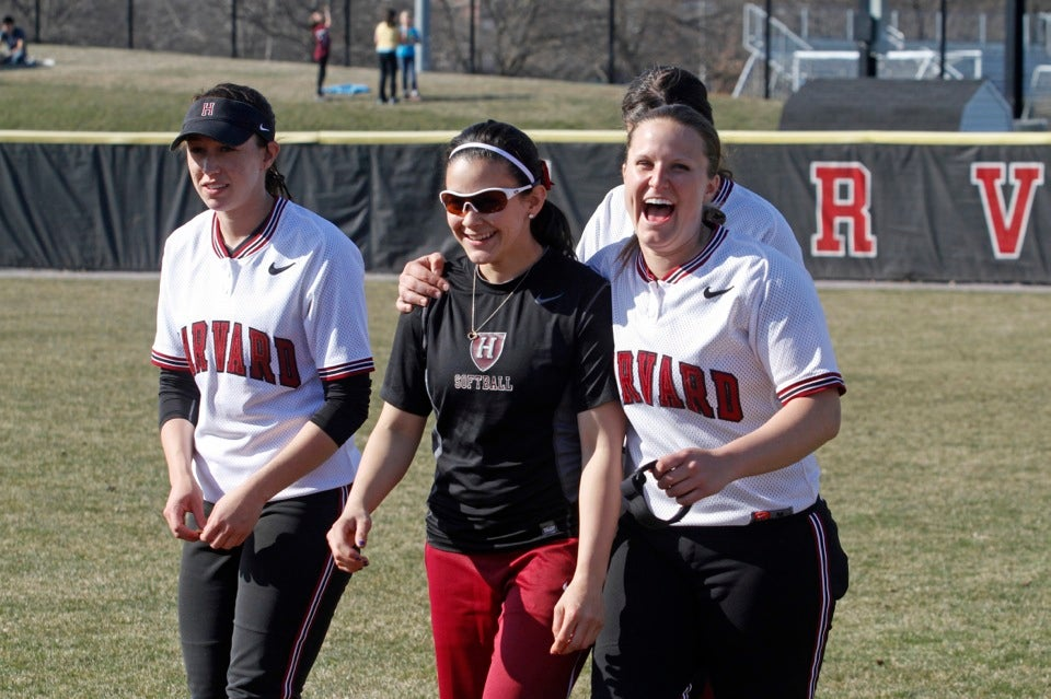 Haley Davis '16 (from left), Zoe Galindo '16, and Stephanie Regan '13 are in high spirits as they break from a team huddle before the second game of their doubleheader.