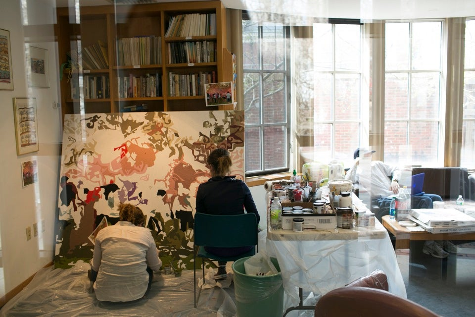 Gilon (right) and Elena Hoffenberg '16 paint inside Harvard Hillel — the project was routed indoors due to inclement weather.