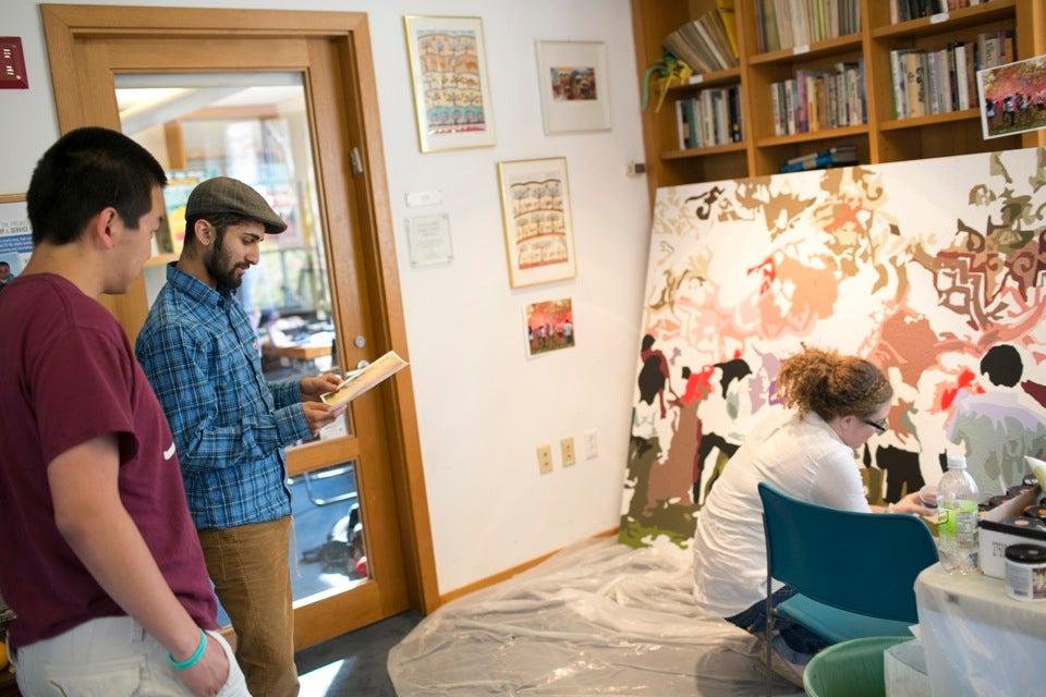 Arun Viswanath '13 (center, blue shirt) checks the mural guide with Sebastian Chiu '13 while Hoffenberg paints.