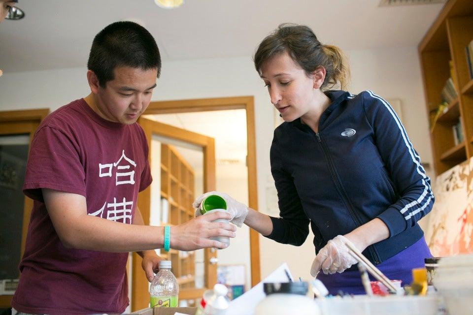Gilon helps Chiu mix paint.