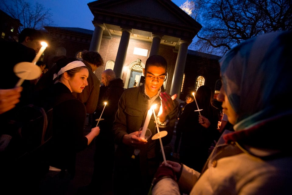 Honor Wilkinson '14 (left) and Andrew Sudler '14 light candles at the Memorial Church vigil Tuesday night.