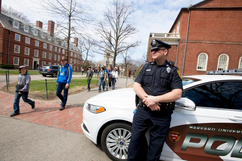 Harvard University Police Department Officer Michael Arsenault stands watch in Harvard Yard.