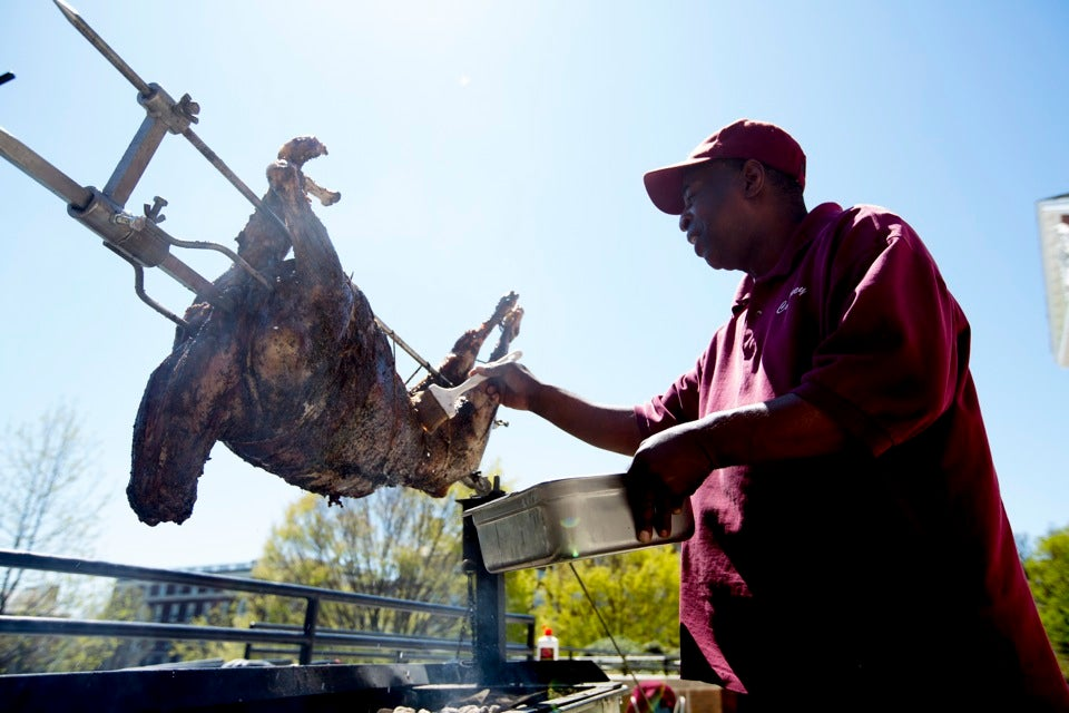 Courtney Evans of Harvard University Dining Services marinates a lamb on a spit for the GreekFest dinner.