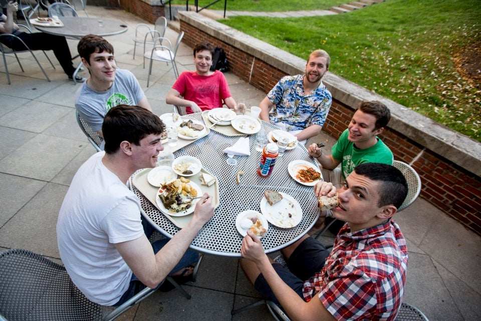 Students James Damiano (clockwise from left), Jurgen Kameniku, John Holland-McCowan, Henney Sullivan, Jonathan Young, and Jacob Montgomery eat on the patio.