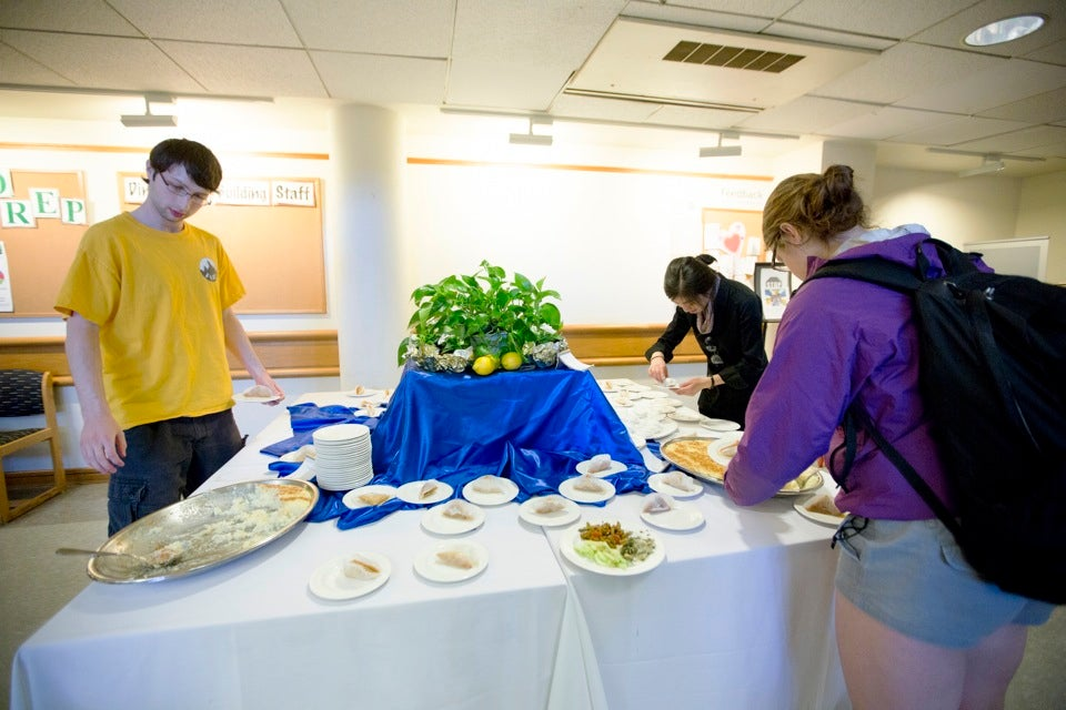 Students peruse — and pluck from — the dessert table.