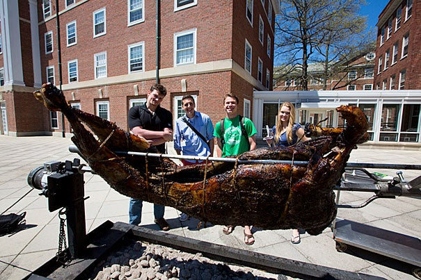 Christopher Valenti (from left), Peter Grogan, Henney Sullivan, and Nicola Maasdorp watch as the lamb is roasted at Pforzheimer House's annual GreekFest.