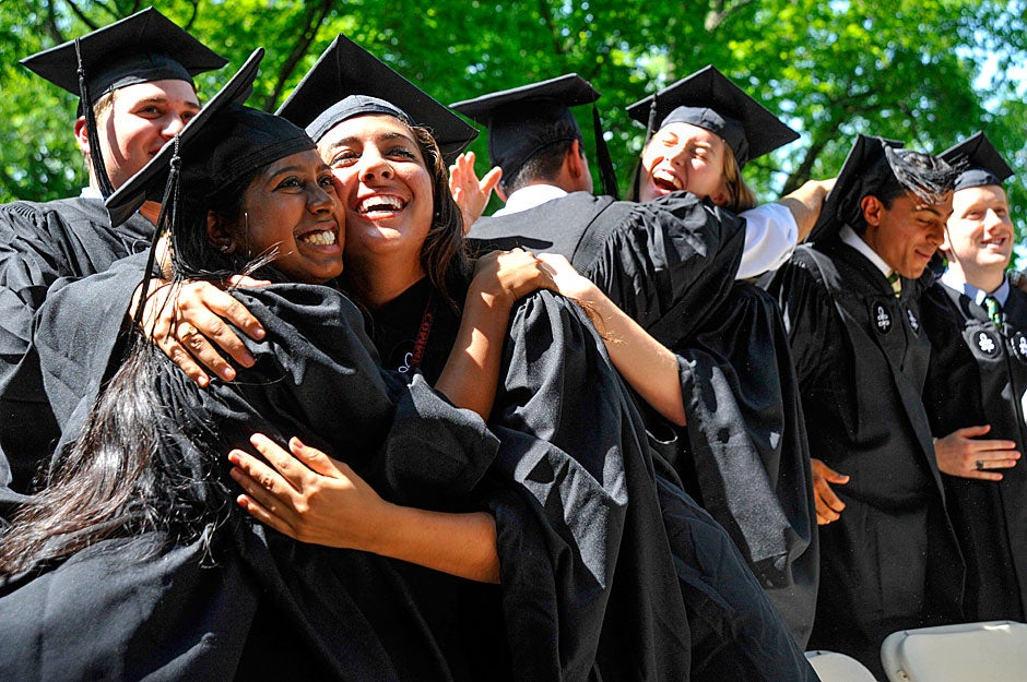 Shalini Pammal (left) and Alexandra Marie Garcia share a hug at the announcement of their degrees. Jon Chase/Harvard Staff Photographer