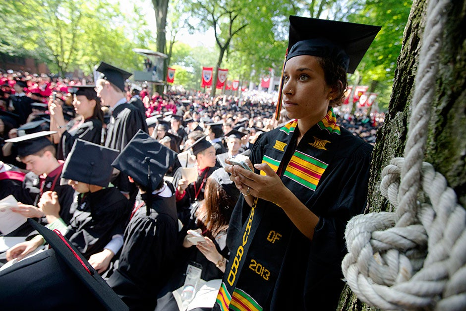 Camille Owens sends a text during Commencement. Kris Snibbe/Harvard Staff Photographer