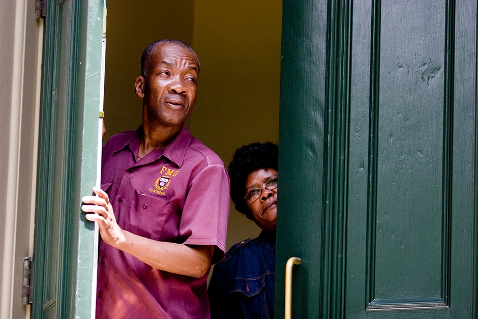 In 2009, Leonvil Altidor (from left) and Andree-Rose Saint-Cyr, custodians in Thayer Hall, watch the Baccalaureate Procession through Harvard Yard. Rose Lincoln/Harvard Staff Photographer