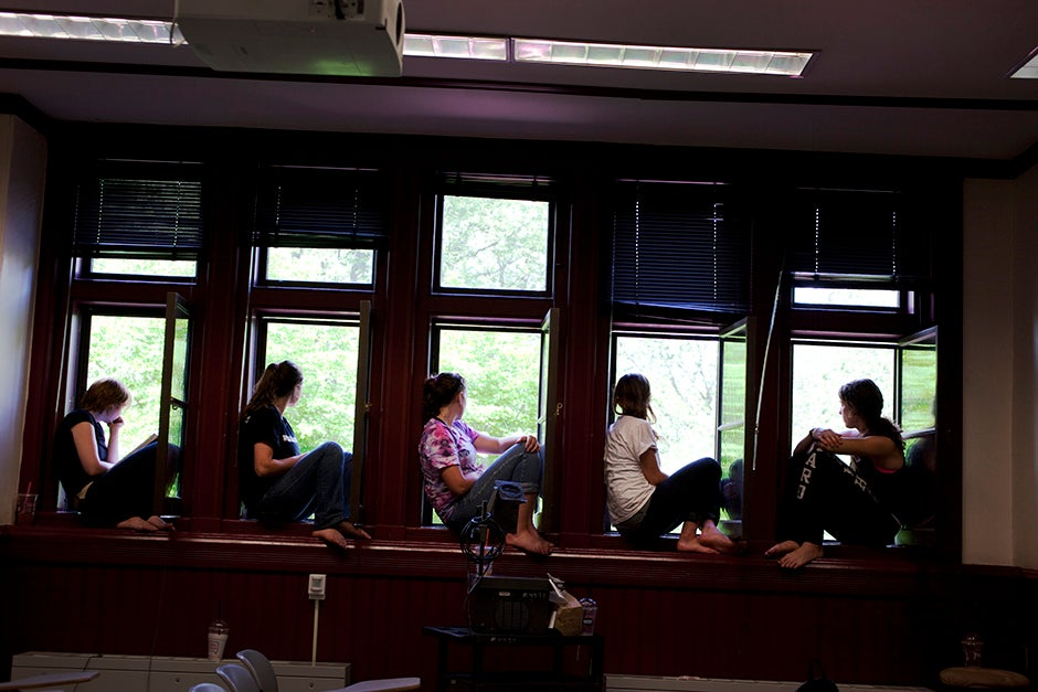 Miranda Shugars '14 (from left), Steph Hadley '15, Kathryn Reed '13, Leonie Oostrom '15, and Christine Mansour '15, all members of dorm crew, take a break to watch the ceremony from the windows of Sever Hall during the 2012 Commencement. Rose Lincoln/Harvard Staff Photographer