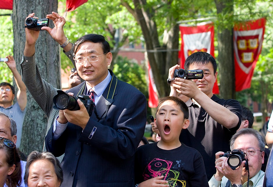 John Xi (left), from Chicago, father of Joy Xi '09, joins other parents in photographing their kids during the Class of 2009 official class photo, while son Matt, age 10, can't stifle a yawn during the proceedings. Jon Chase/Harvard Staff Photographer