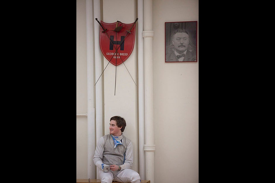 Tommaso DiRobilant, a first-year from Rome, Italy, takes a breather while practicing with The Harvard Fencing team inside the Malkin Athletic Center at Harvard University. On the right is a photo of M. Pierre Pianelli who a fencing instructor--under his coaching tenure Harvard started it's official dual meet schedule (1901/02).   Staff Photo Kris Snibbe/Harvard University