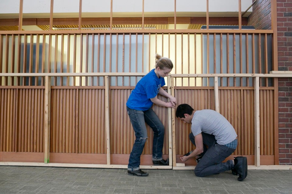 It takes two to make a thing go right! Ella Gibson '14 and David Campos '14 line the Mather House dining hall with plywood boxes, to which heavy-duty plastic will be stapled.