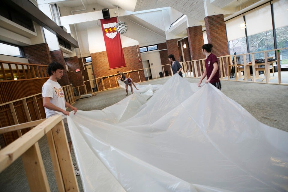Students roll out tarp to weather the foamy storm.