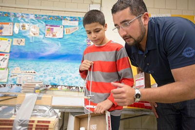 SEAS research and education specialist Jorge Pozo works on a presentation with Juan Nazario at the Hennigan Elementary School in Jamaica Plain.