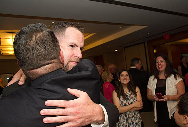 """Officer Ryan Stanton gets a congratulatory hug after receiving a Medal of Valor. He and Officer Michael Rea were awarded the honor for demonstrating """"outstanding courage and valor"""" in the face of danger by exposing themselves to gunfire in order to administer first aid to wounded MBTA officer Dick Donahue, ultimately saving Donahue's life."""