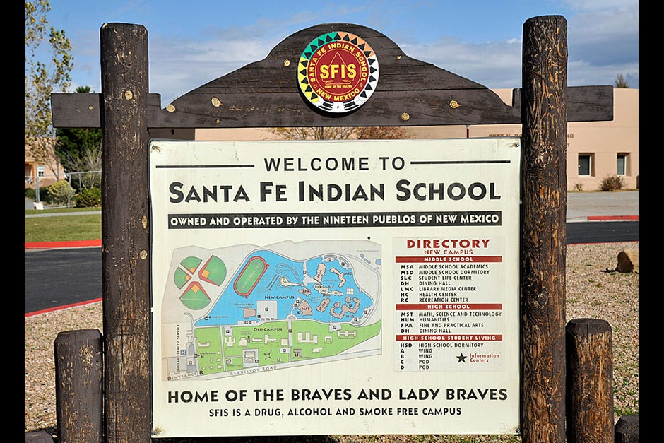 A sign welcomes visitors to the Santa Fe Indian School, originally founded as a boarding school in 1890 by the Bureau of Indian Affairs. Throughout the school's early history, young Native American children were removed from their families and forced to attend. Now the school is a much sought-after destination for youths both in and out of state who want a quality education. Jon Chase/Harvard Staff Photographer