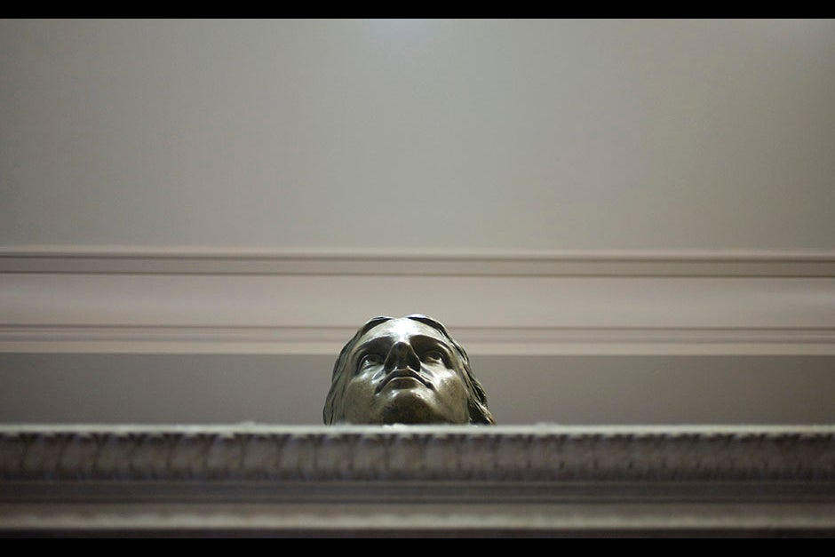 A head above. Here, John Harvard gazes over the Thompson Room fireplace in the Barker Center. Stephanie Mitchell/Harvard Staff Photographer