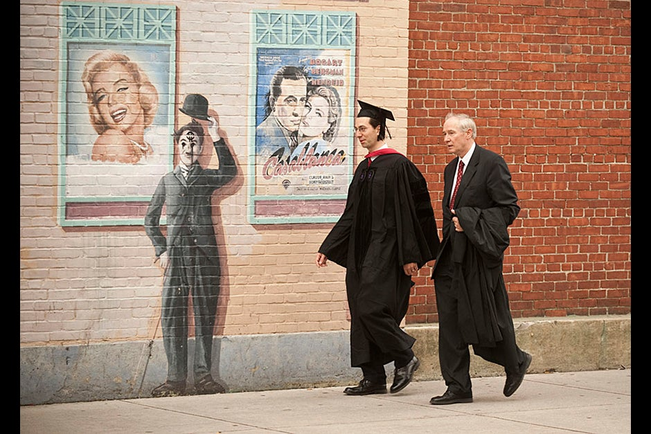 Christoph Luschin and his father, Hanno, from the Ukraine, walk past a mural on Brattle Street of Charlie Chaplin doffing his hat. Luschin graduated from the Law School. Jon Chase/Harvard Staff Photographer