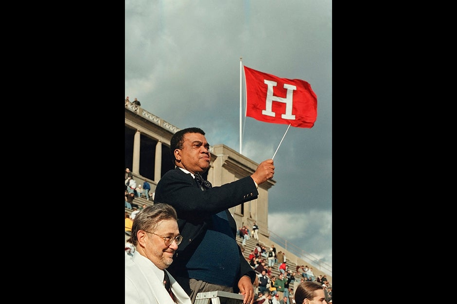 Archie Epps, Harvard College dean of students, conducts the Harvard University Band during half time at the Harvard-Yale football game in 1998, as band director Tom Everett looks on. Epps served as dean for 28 years, while Everett has been the longest serving director of the Harvard University Band since coming to Harvard in 1971.