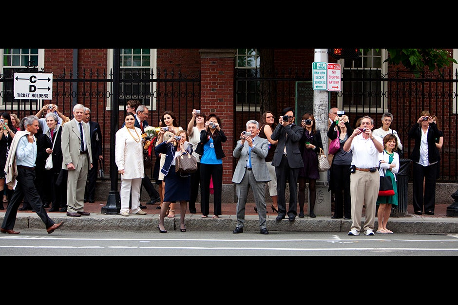 Parents and family members stand along Massachusetts Avenue waiting for a glimpse of their graduates as they process into Tercentenary Theatre in 2010. Actress Meryl Streep was one of the honorary degree recipients during the morning exercises. Rose Lincoln/Harvard Staff Photographer