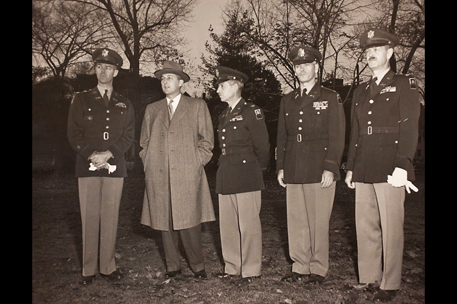 Copy image of historical material gathered from Harvard University Archives regarding the university's history with ROTC. The image inscription verso reads, Reviewing ROTC parade at Harvard University are (left to right): Lt. Col Trevor H. Dupuy, Senior Professor of Military Science and Tactics of Harvard University; President Nathan M Pusey of Harvard University; Colonel Henry J.P. Harding, Chief Massachusetts Military District; Colonel Frank M. Foley, Senior Army Advisor Massachusetts Military District and Major Henry P. Walker, Professor of Military Science and Tactics at Harvard University. November 6, 1953. Credit: U.S. Army Photograph. Stephanie Mitchell/Harvard Staff Photographer