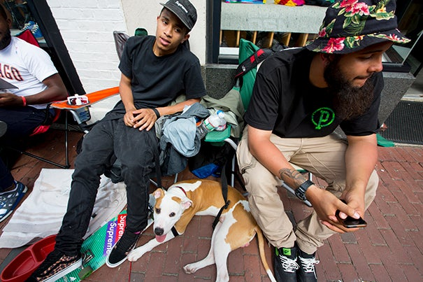 "Kamal Malik (center) and friends Max the dog, Robin Brown (right), and Corey Lewis (left) camped in front of Concepts shoe store to score limited-edition Harvard-themed sneakers (photo 1). New Yorkers David Medrano (from left), Bidhan Roy, Kevin Robles, and Alex Velazquez took a break from the sidewalk campsite to go for a ride (photo 2). Concepts' storefront, where the line for the Asics ""Three Lies"" sneaker begins (photo 3)."