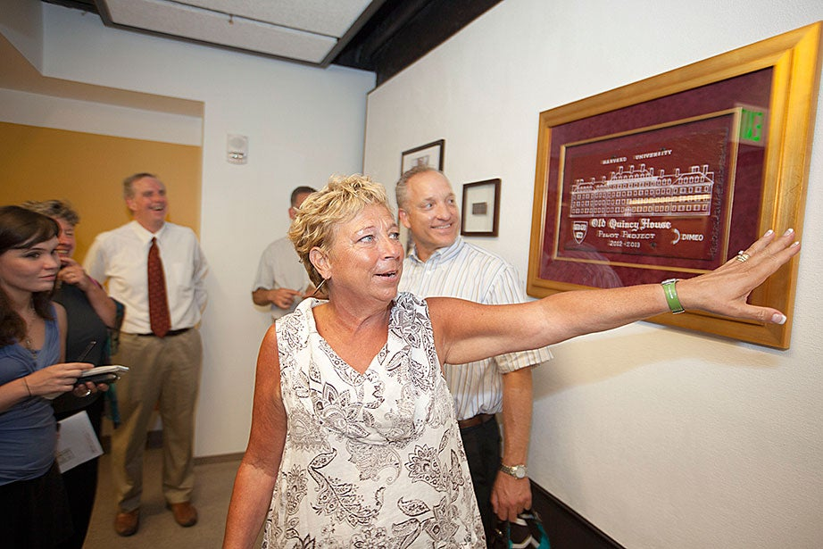 """Deb Gehrke, Quincy House Master, shows House memorabilia outside a """"smart classroom"""" as Faculty of Arts and Sciences Dean Michael D. Smith and architect Stephen Kieran (far left) look on during a tour of the newly renovated Old Quincy House."""