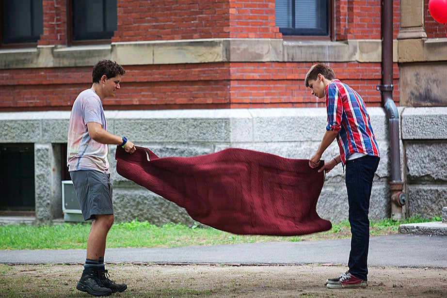 Shai Szulanski '17 and Zachary Chauvin '17 shake out a carpet in front of Weld Hall.