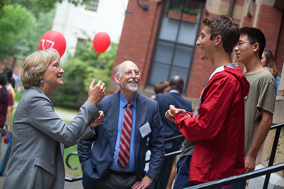Harvard President Drew Faust (from left) and interim Dean of Harvard College Donald Pfister greet Michael Albergo '17 and Roger Zou '17 as they move into Weld Hall.
