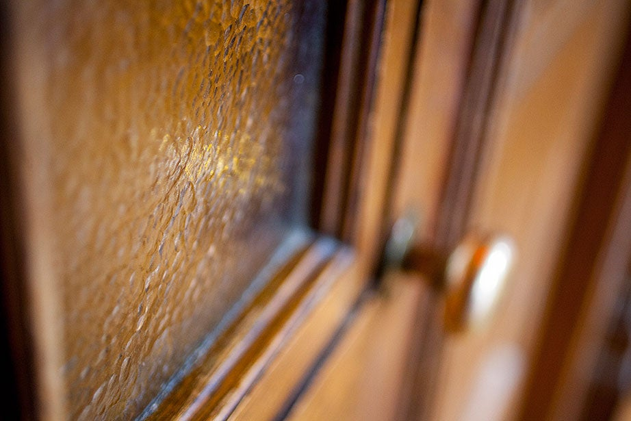 Textured gold-colored glass is framed inside two oak doors on the third floor of the chapel.