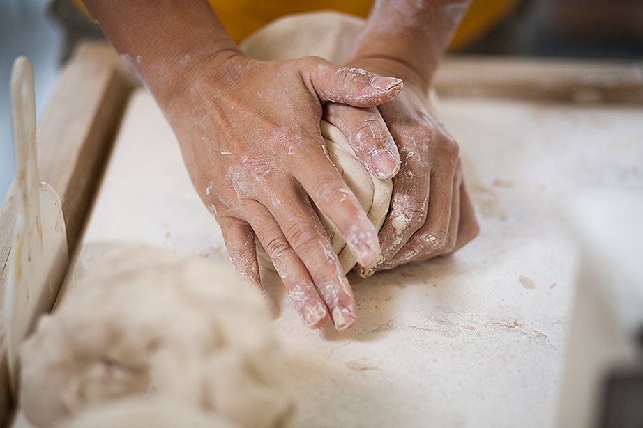 Casey Zeng wedges his porcelain clay.
